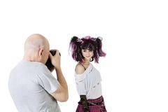 Senior photographer in shooting fashion model over white background Royalty Free Stock Image