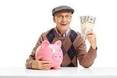 Senior with piggybank and money bundles sitting at a table. Senior with a piggybank and money bundles sitting at a table isolated on white background Stock Image