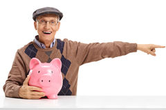 Senior with a piggybank sitting at a table and pointing right. Isolated on white background Stock Photos