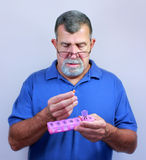 Senior with Daily Pill Dispenser. An adult man lifts a pill to his mouth from a daily pill dispener Stock Photos