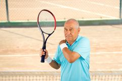 Senior player with pain in shoulder. Shot of a tennis player with a shoulder injury on a clay court Royalty Free Stock Photos
