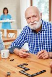 Senior playing Alzheimer`s at Domino. Senior with dementia or Alzheimer`s playing in retirement home at domino stock images