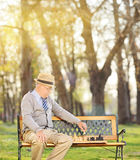 Senior playing chess alone in park Stock Image