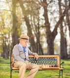 Senior playing chess alone seated on bench in park Stock Image
