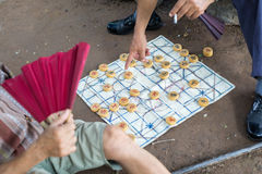 Senior playing chinese chess on the ground Stock Image