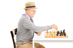 Senior playing a game of chess seated at table Stock Photo