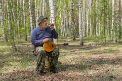 Senior playing music in birch forest Royalty Free Stock Images