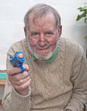 Senior playing with toy gun Stock Image