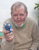 Senior playing with toy gun stock image