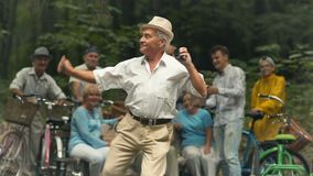 Old man dances in the park. Senior pleasant man is in the park. Old man holds loudspeaker in his hands and dances. Old-aged man smiles and enjoys himself. Other