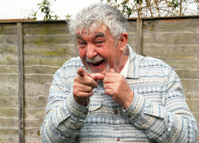 Senior pointing and laughing. stock photo
