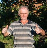 Senior poor man showing yes sign. On natural background stock photography