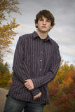 Senior Portrait Along Trail. Young male high school senior in a casual pose standing along edge of park trail with colorful autumn leaves in background stock photo