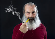 Senior portrait with white beard and pipe. On black Stock Image