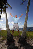 Senior posing by palm trees Royalty Free Stock Photo