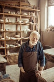 Senior potter in apron standing and leaning on table against shelves with pottery goods at workshop Royalty Free Stock Photos