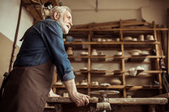 Senior potter in apron standing and leaning on table against shelves with pottery goods at workshop Stock Images