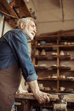 Senior potter in apron standing and leaning on table against shelves with pottery goods at workshop Royalty Free Stock Photography