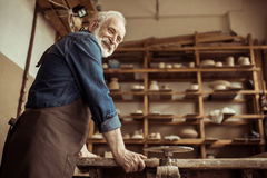 Senior potter in apron standing and leaning on table against shelves with pottery goods at workshop Stock Photography