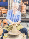 Senior potter shaping up the clay pot on wheal Royalty Free Stock Images