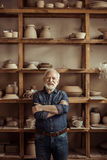 Senior potter standing against shelves with pottery goods at workshop. Front view of senior potter standing against shelves with pottery goods at workshop Stock Photo
