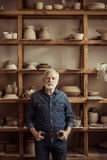 Senior potter standing against shelves with pottery goods at workshop Royalty Free Stock Photography