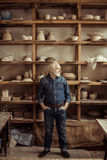 Senior potter standing against shelves with pottery goods at workshop Stock Image