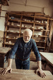 Senior potter standing and leaning on table against shelves with pottery goods at workshop Stock Photos