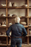 Senior potter standing near shelves with pottery goods and searching something at workshop Stock Photos