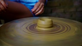 Senior potter starts making clay pot on wheel girl continues. Closeup experienced old master wrinkled hands start making clay pot on rotating potter wheel girl stock footage