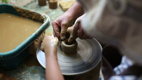 Senior potter teaching happy little girl the art of pottery. Child working with clay, creating modeling ceramic pot on sculpting wheel. Mentoring generations stock footage