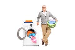 Senior pozuje obok pralki obraz royalty free