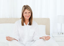 Senior practicing yoga on her bed Royalty Free Stock Photo