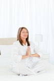 Senior practicing yoga on her bed Royalty Free Stock Photography
