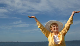 Senior praise. A senior woman stands with arms above head in a praise pose royalty free stock photography