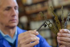 Senior professional with different types keys in locksmith. Senior professional with different types of keys in locksmith royalty free stock images