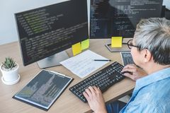 Senior Professional programmer working at developing programming and website working in a software develop company office, writing. Codes and typing data code royalty free stock image