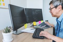 Senior Professional programmer working at developing programming and website working in a software develop company office, writing. Codes and typing data code stock photography