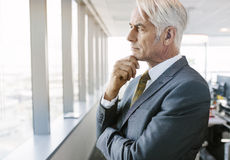 Senior professional thinking for solutions. Side view shot of mature businessman standing beside office window looking outside and thinking with hand on chin Stock Photography