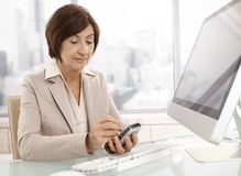 Senior professional woman using pda in office. Sitting at desk, smiling Royalty Free Stock Images