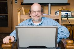 Senior professor with laptop. Senior mature bald multimedia professor with glasses smiling gently and sitting in an armchair in his campus lab or library Stock Photography