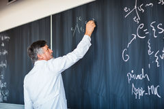 Senior  professor writing on the board Stock Photos
