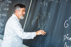 Senior  professor writing on the board Royalty Free Stock Image