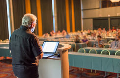 Senior public speaker giving talk at scientific conference. Royalty Free Stock Photo