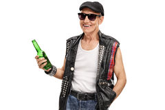 Senior punk rocker holding a beer. Senior punk rocker with a leather vest with pins holding a bottle of beer isolated on white background Stock Photo