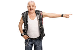 Senior punk rocker pointing to the right. Studio shot of a senior punk rocker pointing to the right isolated on white background Stock Photos