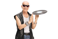 Senior punk rocker spinning a vinyl. On his finger and looking at the camera isolated on white background Royalty Free Stock Photo
