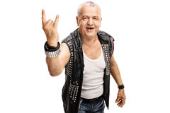 Senior punker making a hardcore gesture. Senior punker in a black leather jacket with pins making a hardcore hand gesture isolated on white background royalty free stock photography
