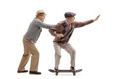 Senior pushing another senior on a skateboard Royalty Free Stock Images
