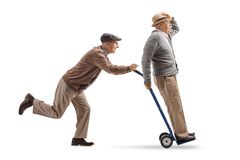 Senior pushing a hand truck with another senior riding on it. Full length profile shot of a senior pushing a hand truck with another senior riding on it isolated Stock Image